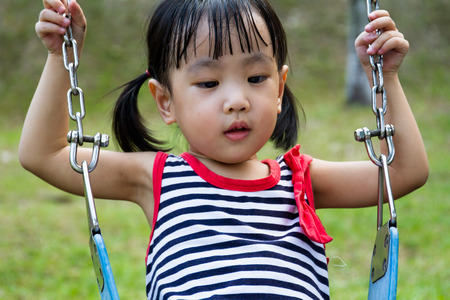 asian children: Asian Chinese little girl swing at outdoor park. Stock Photo