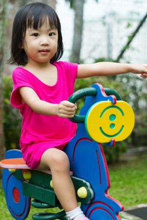 cavallo di troia: Bambina asiatica cinese di equitazione cavallo di troia al parco