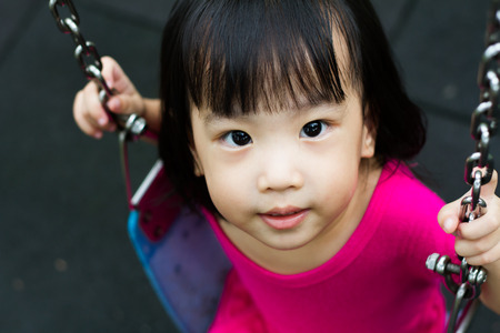 girl on swing: Asian Chinese little girl swing at outdoor park. Stock Photo
