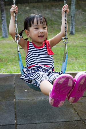Asian Chinese little girl swing at outdoor park. Stock Photo