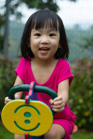 persona alegre: Asia niña china que monta caballo de Troya en el parque Foto de archivo