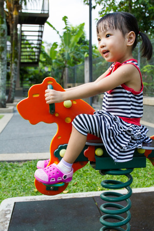 trojan horse: Asian Chinese little girl riding trojan horse at park Stock Photo