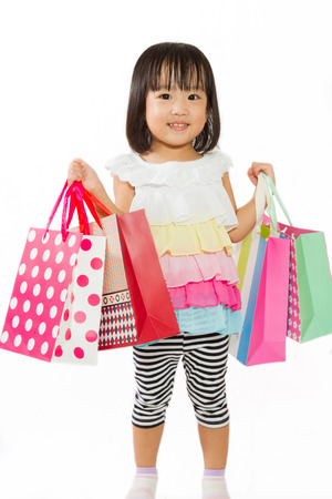happy shopping: Asian Chinese little girl with shopping bag in white isolated background.