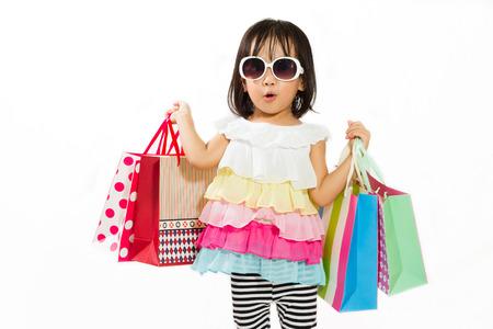 Niña china asiática con el bolso de compras en fondo blanco aislado.