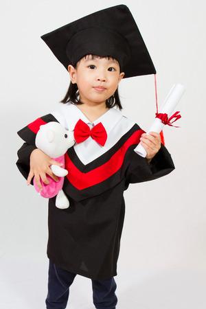 young students: Poca graduación de la muchacha china en el fondo blanco