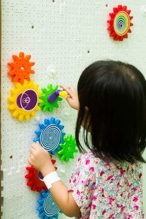 An Asian Chinese girl solving puzzle at indoor playground. Stock Photo