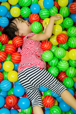 ground: Asian Chinese girl hide in colorful ball pool at indoor playground.