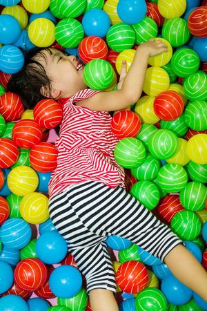 terreno: Asian nascondere Ragazza cinese in piscina di palline colorate a parco giochi al coperto.