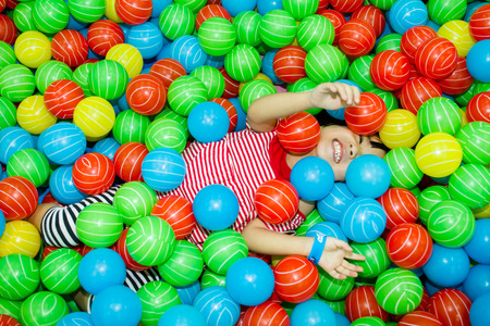 Asian Chinese girl hide in colorful ball pool at indoor playground.