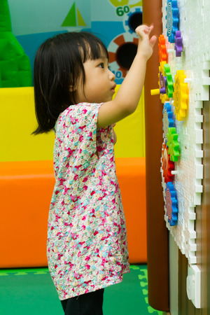 education choice: An Asian Chinese girl solving puzzle at indoor playground. Stock Photo