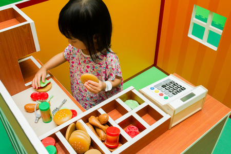 roleplaying: Asian Chinese little girl role-playing at burger store.