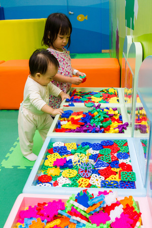 childrens playing: An Asian Chinese childrens playing puzzle at indoor playground. Stock Photo
