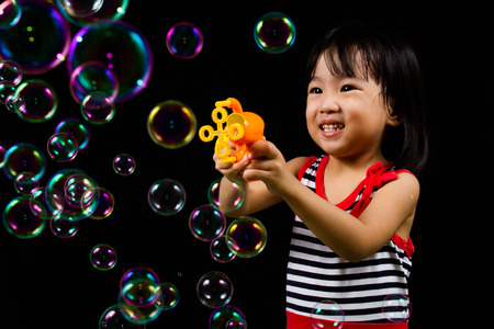 niños negros: Niños chinos asiático que juega burbujas de jabón en el fondo negro de interior.
