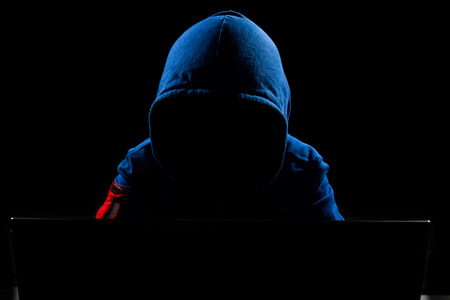 proteccion: Pirata informático sin rostro con ordenador portátil en fondo negro aislado. Foto de archivo