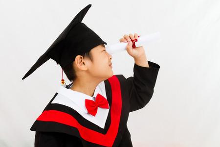 Feier: Chinese kleinen Jungen Graduierung in weißen Hintergrund Studio gedreht. Lizenzfreie Bilder