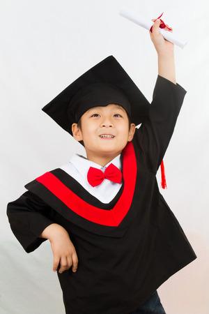 graduacion niños: Poca graduación del muchacho chino en blanco foto de estudio apaisada. Foto de archivo
