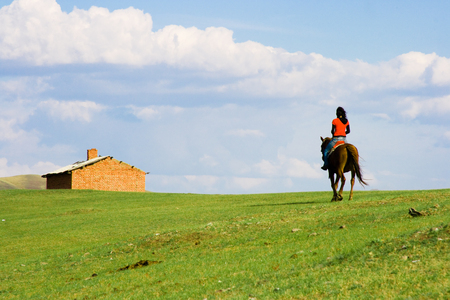 nomadism: Girl ridding horse toward a house in grassland. Stock Photo