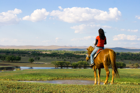 nomad: A young girl ridding horse in grassland.