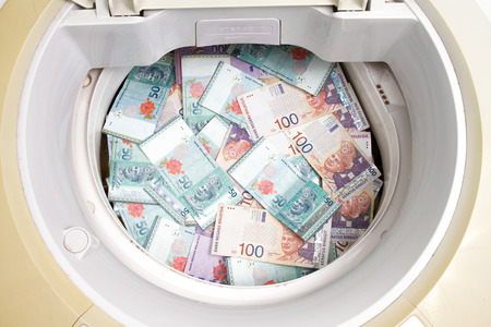 launder: Money laundering concept with Ringgit Malaysia notes in washing machine.