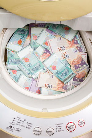 Money laundering concept with Ringgit Malaysia notes in washing machine.