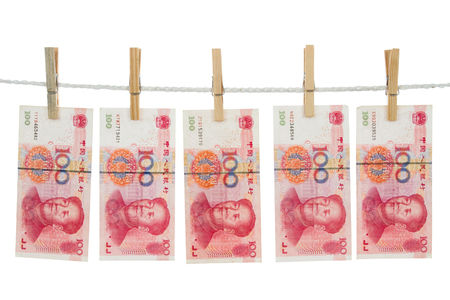Money laundering concept with China notes on clothesline in plain isolated white background.