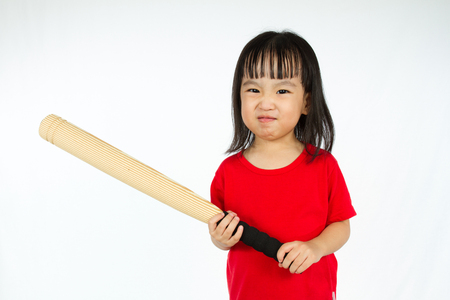 huffy: Portrait of a young little Chinese girl holding baseball bat with angry expression in white isolated background.