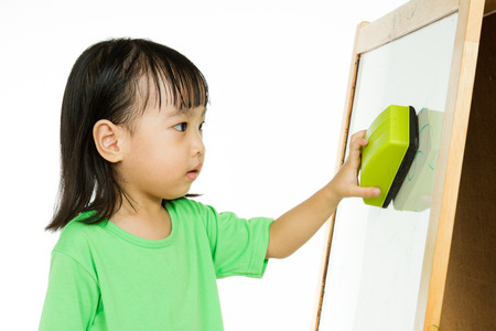 preschooler: Happy cute Asian Chinese toddler girl drawing or writting with marker pen on a blank whiteboard at home, preschool, daycare or kindergarten in plain white isolated background.