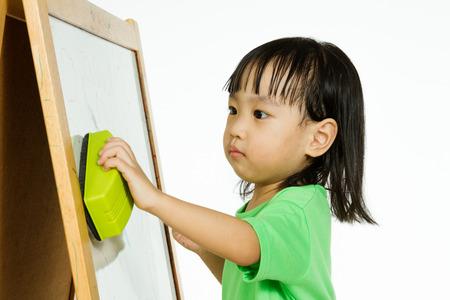 marker: Dibujo Feliz linda asiática china niña niño o escritura con rotulador en una pizarra en blanco en casa, preescolar, guardería o jardín de infancia en el fondo aislado blanco liso.