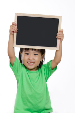 holdings: Asian Chinese children holding balckboard in plain isolated white background. Stock Photo