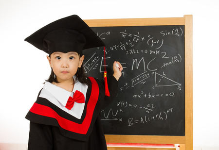 gown: Asian Chinese children in graduation gown againts blackboard or chalkboard with formulas in plain isolated white background.