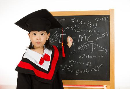 birrete de graduacion: Niños chinos asiáticos en traje de graduación againts pizarrón o pizarra con fórmulas en llanura de fondo blanco aislado.