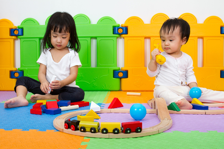 preschooler: Two Asian Chinese little girls playing with blocks and toys train on the floor at kingdergarten. Stock Photo
