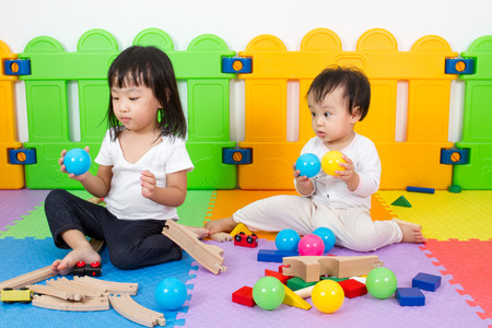 baby playing: Two Asian Chinese little girls playing with blocks and toys train on the floor at kingdergarten. Stock Photo