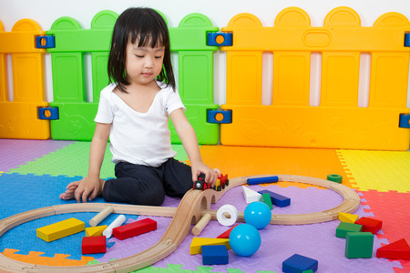 baby sit: Asian Chinese little girl playing with blocks and toys train on the floor at kingdergarten.