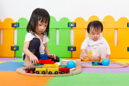Two Asian Chinese little girls playing with blocks and toys train on the floor at kingdergarten. Imagens