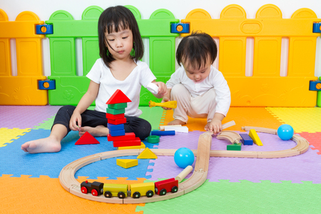 Two Asian Chinese little girls playing with blocks and toys train on the floor at kingdergarten. Stock Photo