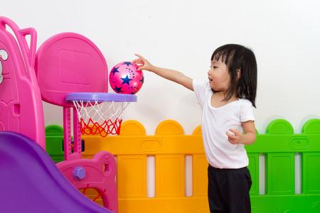 baloncesto chica: Baloncesto poco de juego chino de la muchacha asiática en la zona de juegos de colores de interior
