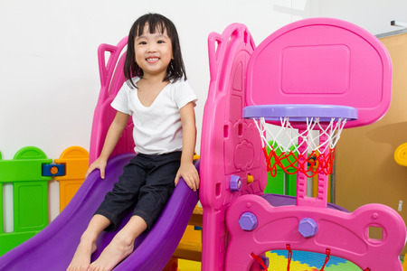ni�os jugando: Asian Chinese little girl playing on the slide at indoor colourful playground.