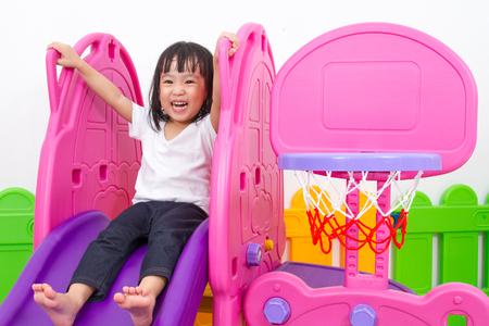ni�os sanos: Ni�a asi�tica china que juega en la diapositiva en el patio interior colorido. Foto de archivo
