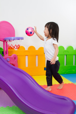 child ball: Asian Chinese little girl playing basketball at indoor colourful playground
