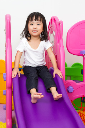 people in action: Asian Chinese little girl playing on the slide at indoor colourful playground.
