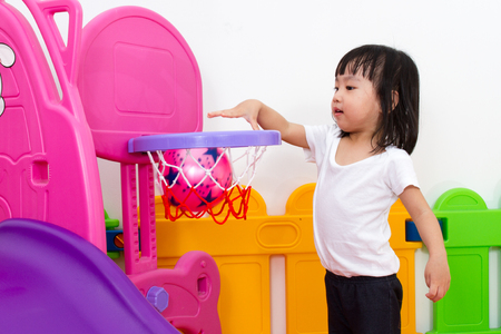 children sport: Asian Chinese little girl playing basketball at indoor colourful playground