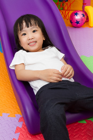 toddler playing: Asian Chinese little girl playing on the slide at indoor colourful playground.