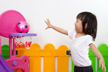 asia children: Asian Chinese little girl playing basketball at indoor colourful playground