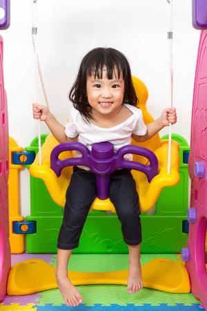 ni�os chinos: Ni�os chinos asi�ticos que juegan en el oscilaci�n en el patio interior. Foto de archivo