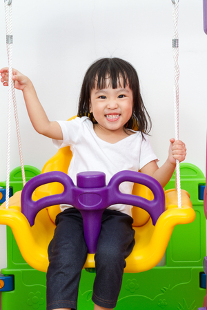 ni�os chinos: Asian Chinese children playing on swing at indoor playground. Foto de archivo