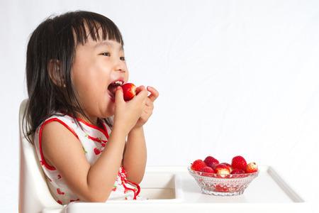 真っ白な背景でイチゴを食べるアジア中国の子供たち。