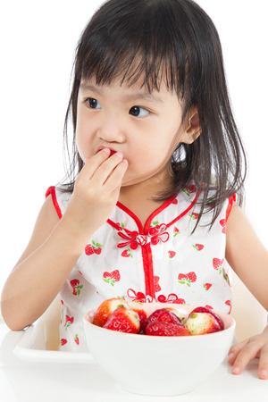 ni�os chinos: Asian Chinese children eating strawberries in plain white background.