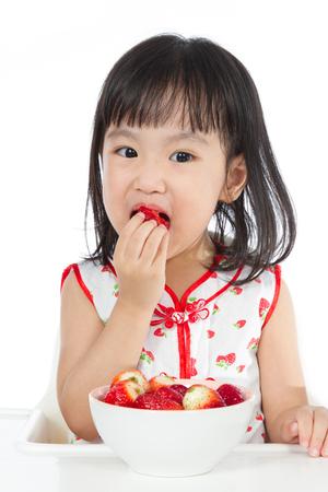 niños sanos: Niños chinos asiáticos comiendo fresas en fondo blanco llano.