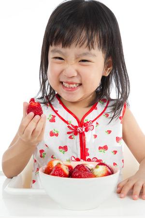 yummy: Asian Chinese children eating strawberries in plain white background.